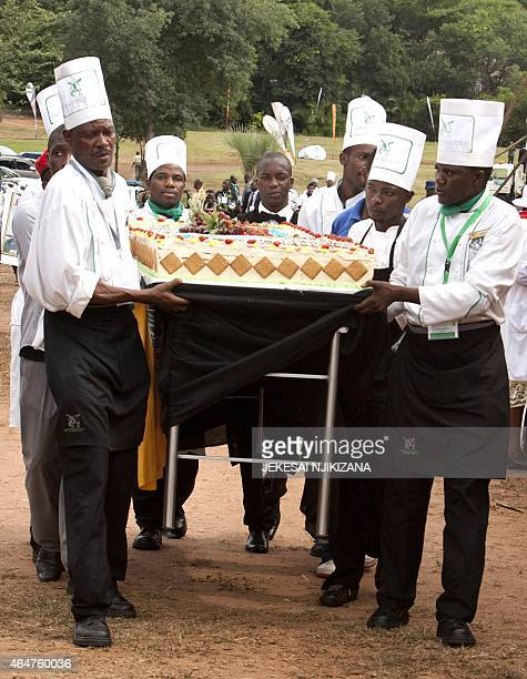 Catering staff carry a birthday cake for the celebration of Zimbabwean President Robert Mugabe's 91st birthday in Victoria Falls Mugabe celebrated...