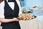 waitress catering service. female staff servicing dish full of snack food at restaurant event