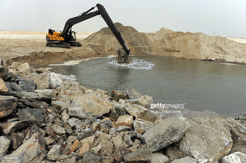 A caterpillar digs reclaimed land from the sea, on January 31, 2013 in Lagos, during the building of the three and a half kilometre long sea defence barrier called 'The Great Wall of Lagos' built to shield from coastal erosion Eko Atlantic, a new city born from the Altantic ocean in Lagos. Nigeria's President Goodluck Jonathan and former US President Bill Clinton dedicated on February 21, 2013 the new 5-million-square-metre Eko Atlantic City, which is to be the first modern smart city in Africa to be built on reclaimed land from the Atlantic Ocean.