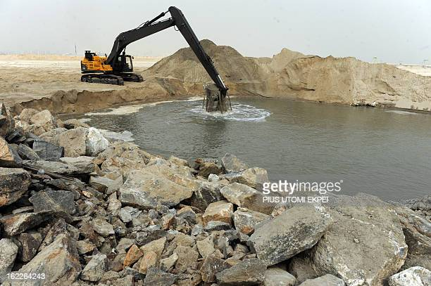 A caterpillar digs reclaimed land from the sea on January 31 2013 in Lagos during the building of the three and a half kilometre long sea defence...