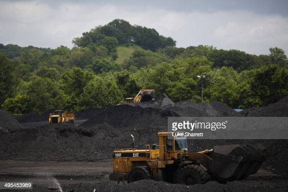 Caterpillar frontloading machinery operates on mounds of coal at Arch Coal Terminals June 3 2014 in Cattletsburg Kentucky New regulations on carbon...