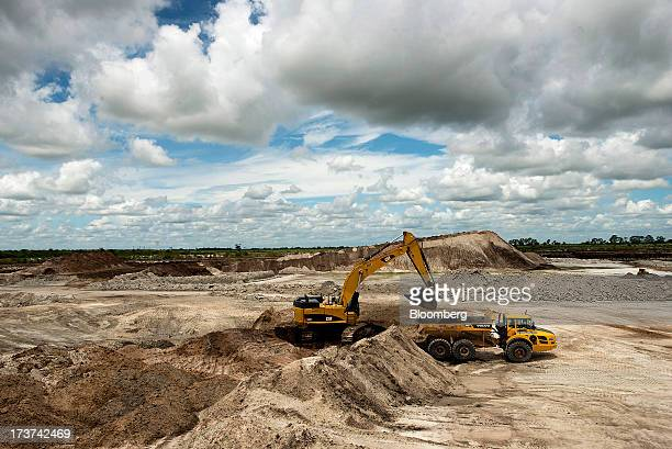 A Caterpillar Inc 374D L hydraulic excavator loads silica sand into a Volvo AG A40F dump truck at the Stewart Mining Plant in Fort Pierce Florida US...