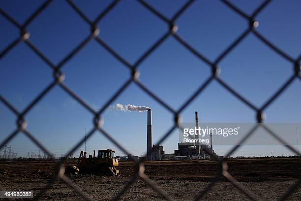 A Caterpillar Inc bulldozer sits parked nearby as emissions rise from a smokestack at the Kentucky Utilities Co EW Brown generating station in...