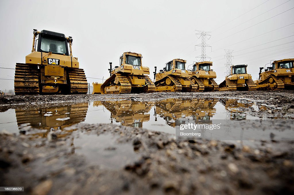 Caterpillar Inc. bulldozers are reflected in a puddle while sitting on display at a Patten Industries Inc. dealership in Elmhurst, Illinois, U.S., on Monday, Jan. 28, 2013. Caterpillar Inc., the largest maker of construction and mining equipment, said gains in its sales and profit this year will come in the second half as the world economy improves. Photographer: Daniel Acker/Bloomberg via Getty Images