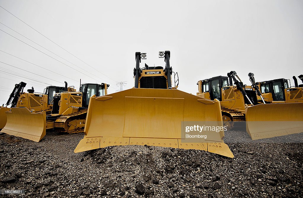 Caterpillar Inc. bulldozers, including a model D6T LGP, center, sit on display at a Patten Industries Inc. dealership in Elmhurst, Illinois, U.S., on Monday, Jan. 28, 2013. Caterpillar Inc., the largest maker of construction and mining equipment, said gains in its sales and profit this year will come in the second half as the world economy improves. Photographer: Daniel Acker/Bloomberg via Getty Images