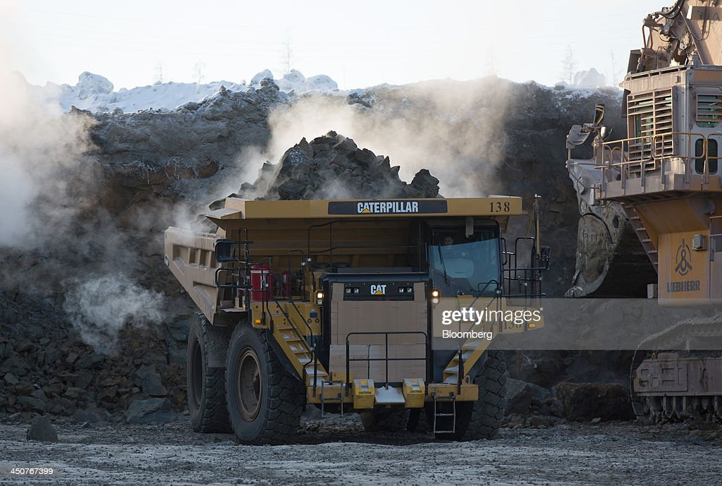 A Caterpillar Inc. dump truck collects diamond ore from an excavator operating in the open pit of the Nyurbinsky diamond mine operated by OAO Alrosa in Nakyn, Russia, on Friday, Nov. 15, 2013. OAO Alrosa, the world's largest diamond producer, raised about $1.3 billion in an oversubscribed share sale from investors including Oppenheimer Funds Inc. and Lazard Ltd.'s asset-management unit, First Deputy Prime Minister Igor Shuvalov said. Photographer: Andrey Rudakov/Bloomberg via Getty Images