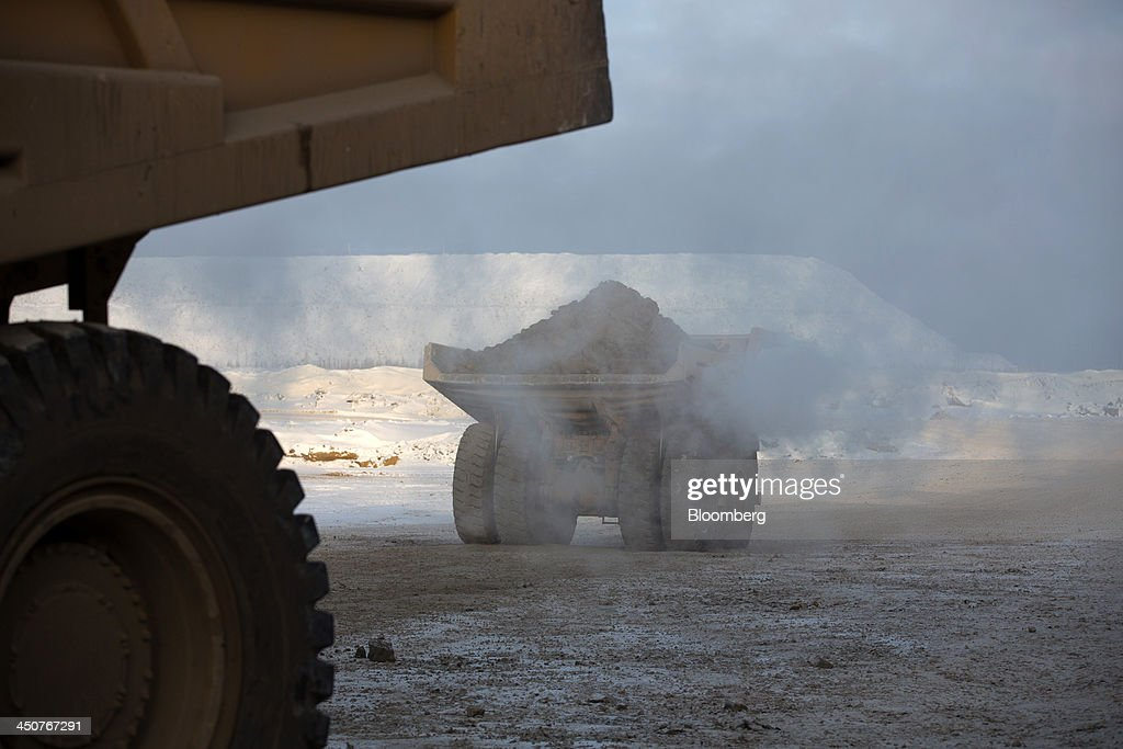 A Caterpillar Inc. dump truck collects excavated diamond ore from an excavator operating in the open pit of the Nyurbinsky diamond mine operated by OAO Alrosa in Nakyn, Russia, on Friday, Nov. 15, 2013. OAO Alrosa, the world's largest diamond producer, raised about $1.3 billion in an oversubscribed share sale from investors including Oppenheimer Funds Inc. and Lazard Ltd.'s asset-management unit, First Deputy Prime Minister Igor Shuvalov said. Photographer: Andrey Rudakov/Bloomberg via Getty Images