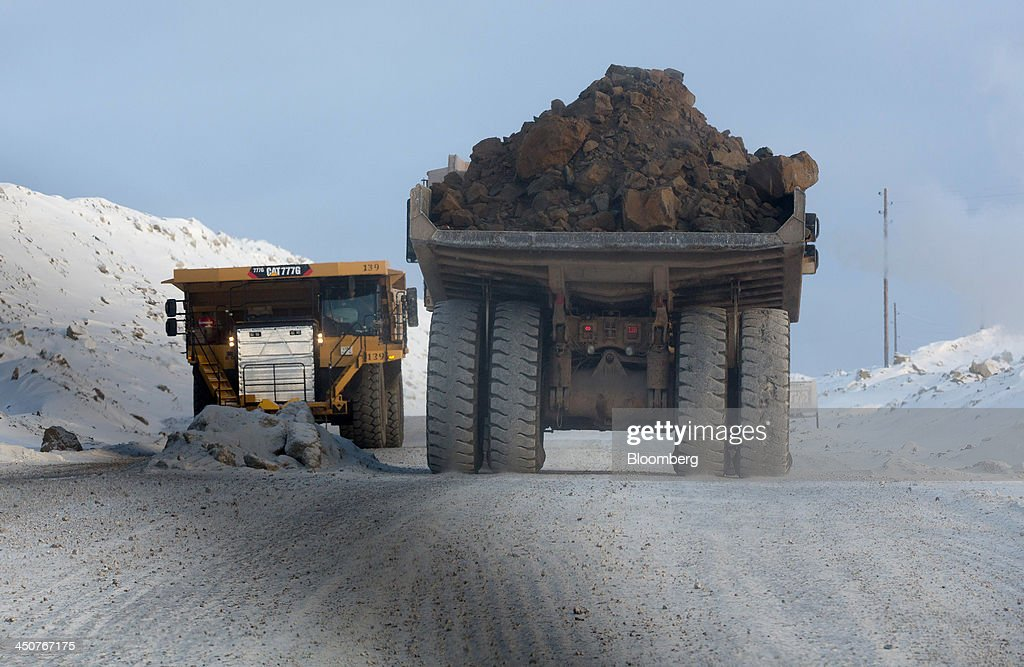 Caterpillar Inc. dump trucks transport excavated diamond ore from the open pit of the Nyurbinsky diamond mine operated by OAO Alrosa in Nakyn, Russia, on Friday, Nov. 15, 2013. OAO Alrosa, the world's largest diamond producer, raised about $1.3 billion in an oversubscribed share sale from investors including Oppenheimer Funds Inc. and Lazard Ltd.'s asset-management unit, First Deputy Prime Minister Igor Shuvalov said. Photographer: Andrey Rudakov/Bloomberg via Getty Images