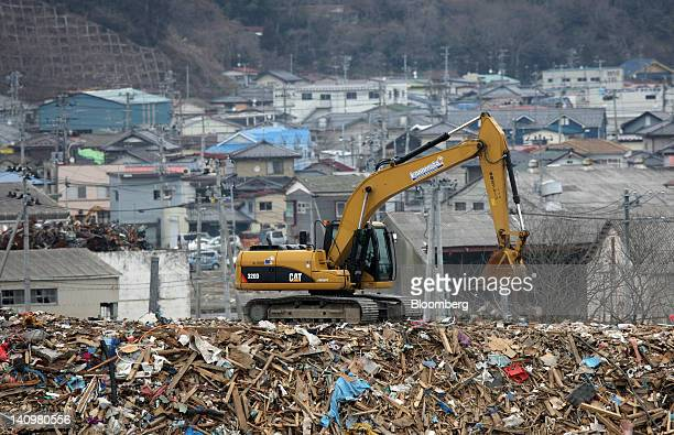 A Caterpillar Inc excavator lords debris from the tsunami which followed the Great East Japan Earthquake on March 11 in Ishinomaki City Miyagi...