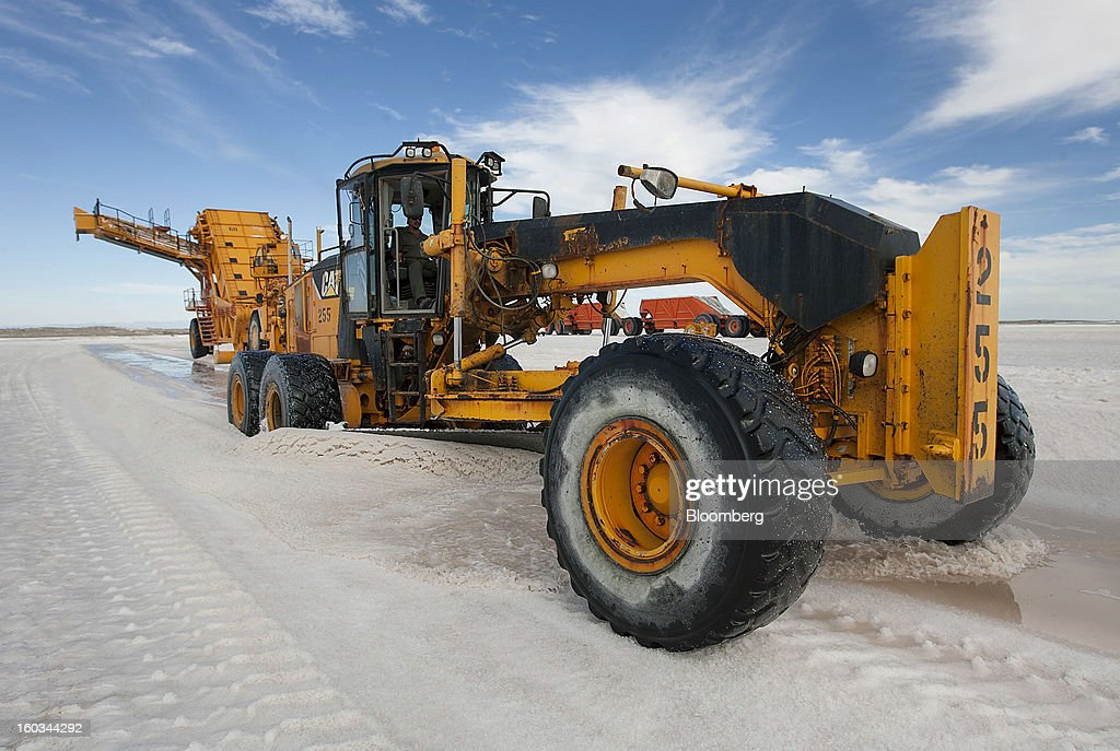 A Caterpillar Inc. Motor Grader makes rows of salt in a crystallization pond at the Exportadora de Sal (ESSA) harvest fields in Guerrero Negro, Mexico, on Wednesday, Jan. 24. 2013. Exportadora de Sal (ESSA), a joint venture between Fidecomiso Mining Development Corporation and Mitsubishi, is one of the leading producers and suppliers of salt for the chlorine-alkali industry in the Pacific Rim. Photographer: Susana Gonzalez/Bloomberg via Getty Images