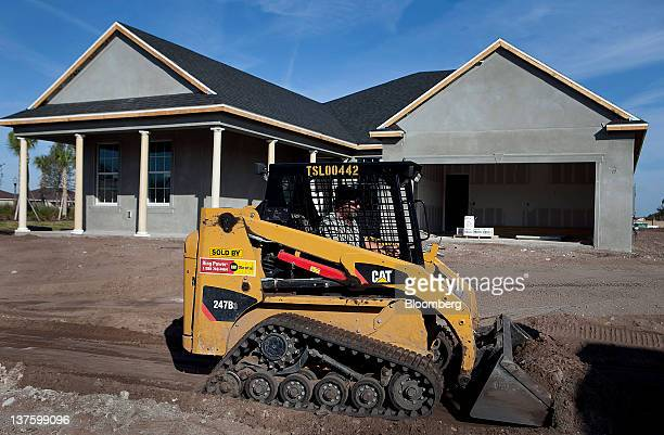 A Caterpillar Inc skid steer loader grades soil at a house under construction at the KB Home Mabel Bridge community in Orlando Florida US on Tuesday...