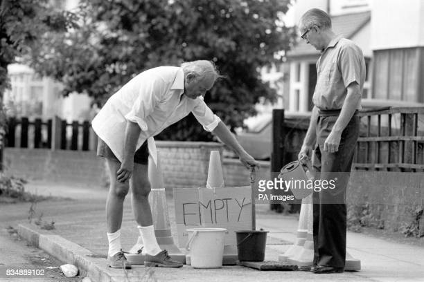 Catford residents Mr Hall and Mr Heighes try in vain to get water from an empty sandpipe in Allerford Road South East London where shortages have...