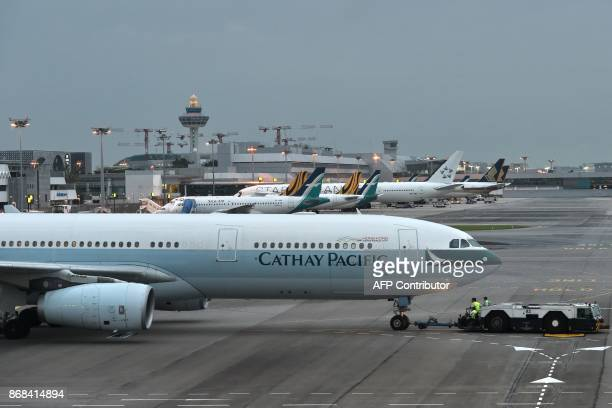 A Cathay Pacific aircraft is towed out at the Changi International airport Terminal 4 for departure in Singapore on October 31 2017 / AFP PHOTO /...