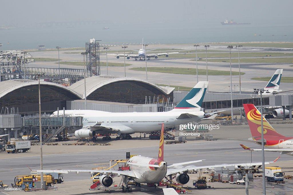 A Cathay Pacific Airways Ltd aircraft center sits on the tarmac at Hong Kong International Airport in Hong Kong China on Tuesday Aug 12 2014 Cathay...