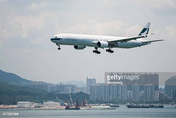A Cathay Pacific Airways Ltd aircraft flies past residential buildings in the Tung Chung area as it approaches to land at Hong Kong International...