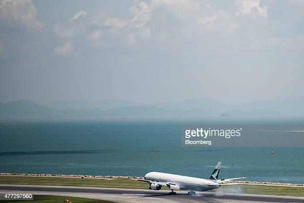 A Cathay Pacific Airways Ltd aircraft touches down on the runway at Hong Kong International Airport in Hong Kong China on Tuesday June 16 2015 The...