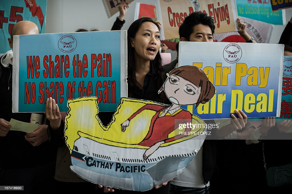 Cathay Pacific flight attendants stage a protest at the international airport in Hong Kong on December 3, 2012. The employees of the Hong Kong flag carrier staged the protest to voice their discontent at the company's decision of an average 2 per cent pay rise for Hong Kong ground staff and cabin crew, claiming it was less than the average 5 per cent rise and below current inflation levels. AFP PHOTO / Philippe Lopez