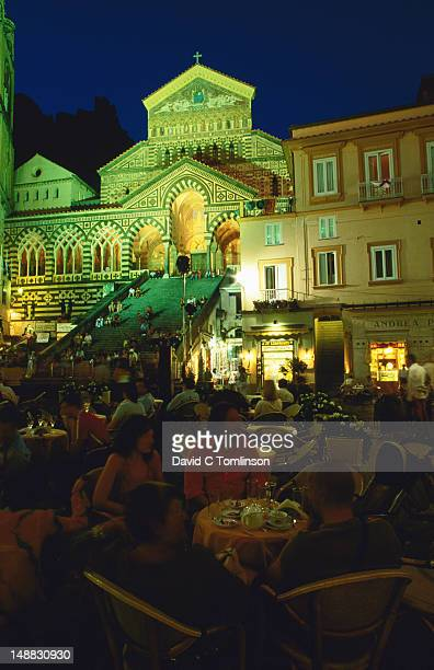 Cathedral illuminated at night with people dining alfresco in foreground, Costiera Amalfitana.