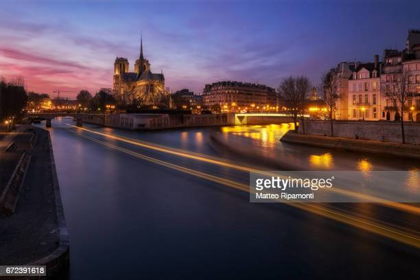 Cathedral of Notre Dame de Paris with Seine river at sunset and light trails of boats