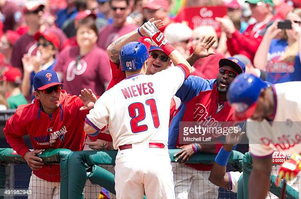 Cather Will Nieves of the Philadelphia Phillies is greeted by cather Carlos Ruiz pitcher AJ Burnett and outfielder Tony Gwynn Jr #19 after Will...