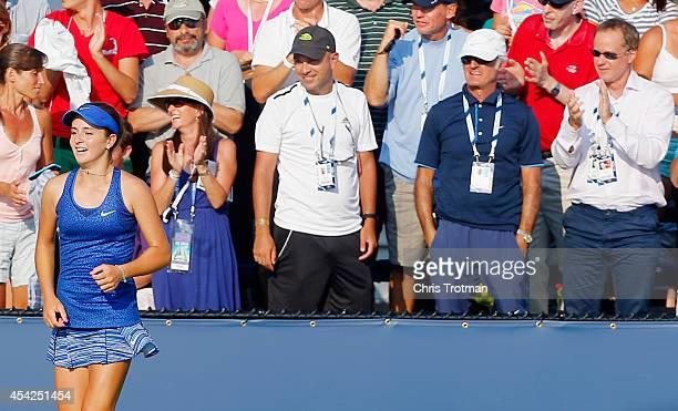 Catherine Bellis of the United States celebrates defeating Dominika Cibulkova of Slovakia during their women's singles first round match as coach Leo...