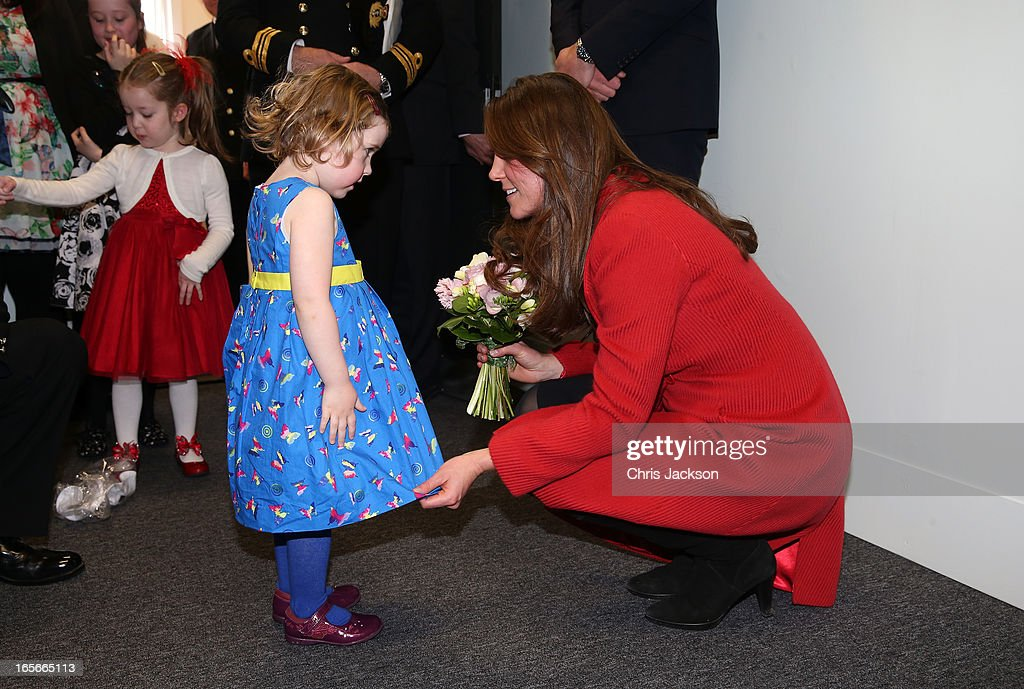 Catherine, Countess of Strathearn helps Maizie Yeardley adjust her dress during a visit the Astute-class Submarine Building at BAE Systems on April 5, 2013 in Barrow-in-Furness, United Kingdom. The Duke of Cambridge is Commodore-in-Chief of the Royal Navy Submarine Service and during their visit they will tour the offices of Vanguard replacement programme and meet with the crew of Artful and their families, who are now based in Barrow.