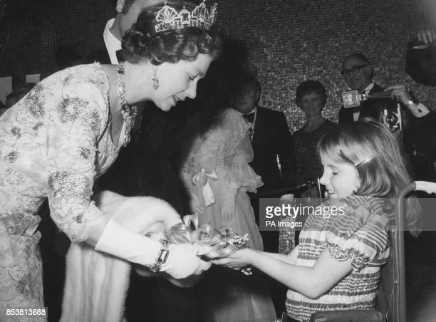 Catherine Cusack of Harrow presents a floral posy to the Queen on her arrival at Leicester Square Theatre The Queen accompanied by Prince Andrew and...