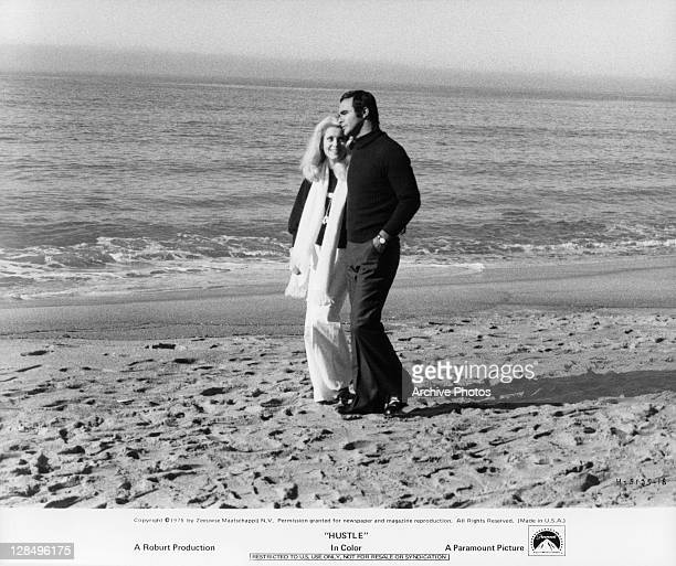 Catherine Deneuve and Burt Reynolds walking on the beach in a scene from the film 'Hustle' 1975