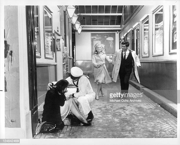 Catherine Deneuve and Nino Castelnuovo happily skip down walkway in a scene from the film 'The Umbrellas Of Cherbourg' 1964