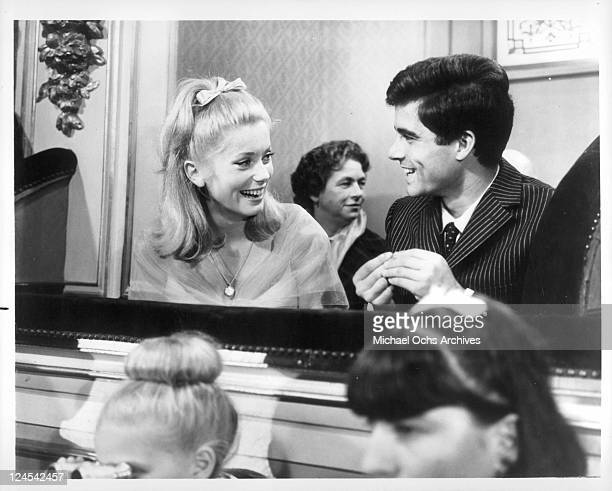 Catherine Deneuve and Nino Castelnuovo share a laugh in a scene from the film 'The Umbrellas Of Cherbourg' 1964