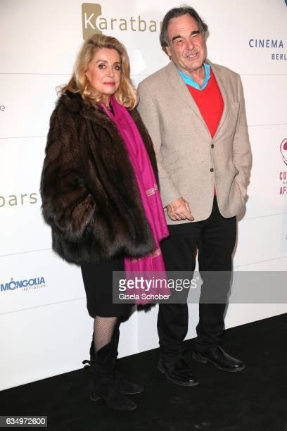 Catherine Deneuve and Oliver Stone during the reception for the Cinema for Peace Foundation at China Club during the 67th Berlinale International...