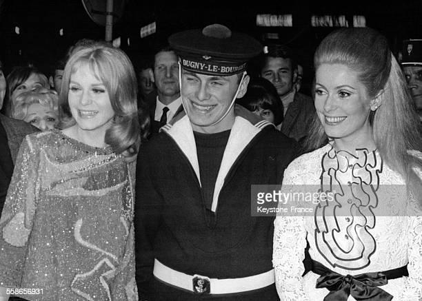 Catherine Deneuve et sa soeur Francoise Dorleac entourant un marin lors de la presentation officielle du film 'Les Demoiselles de Rochefort' de...