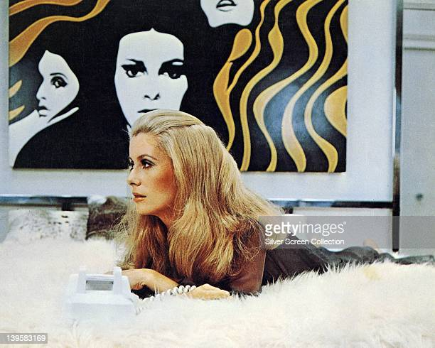 Catherine Deneuve French actress laying on a fur rug on which sits a telephone with an artwork hanging on the wall behind her in a publicity still...