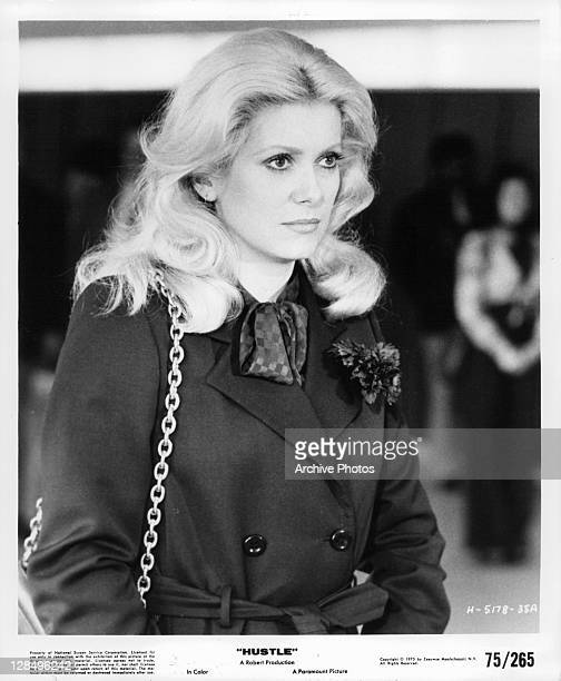 Catherine Deneuve wearing coat in a scene from the film 'Hustle' 1975