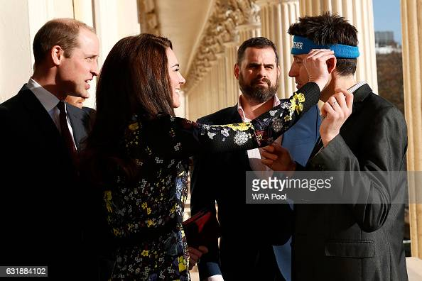 Catherine Duchess Of Cambridge adjusts marathon runner Jon Salmon's headband as Prince William Duke of Cambridge and Steve Jackson look on during an...