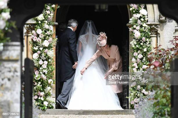 Catherine Duchess of Cambridge adjusts the dress of Pippa Middleton as she enters the church during the wedding of Pippa Middleton and James Matthews...