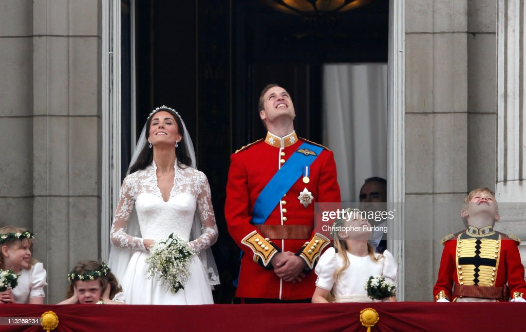 Catherine Duchess of Cambridge and Prince William Duke of Cambridge look up at the flypast on the balcony at Buckingham Palace on April 29 2011 in...