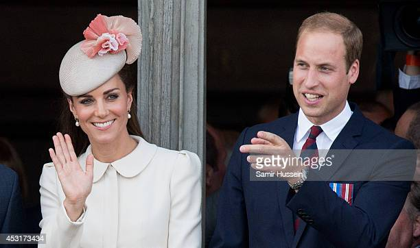 Catherine Duchess of Cambridge and Prince William Duke of Cambridge look on from the balcony of the town hall as they attend a reception at the Grand...