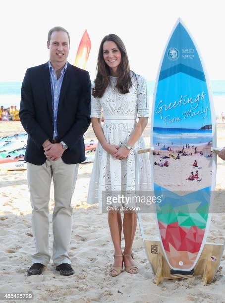Catherine Duchess of Cambridge and Prince William Duke of Cambridge pose with a surfboard they were given as they attend a lifesaving event on Manley...