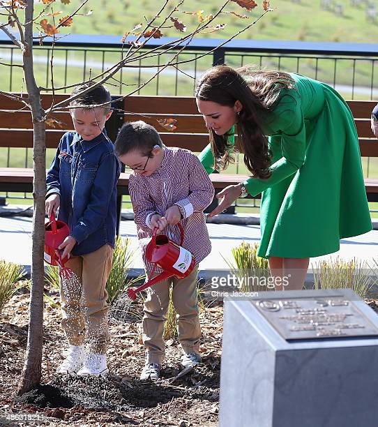 Catherine Duchess of Cambridge and Prince William Duke of Cambridge watch two children help them with a tree planting as they visit the National...