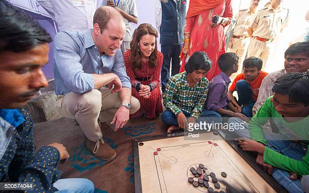 Catherine Duchess of Cambridge and Prince William Duke of Cambridge play a game of carrom with street children at a contact centre run by the charity...