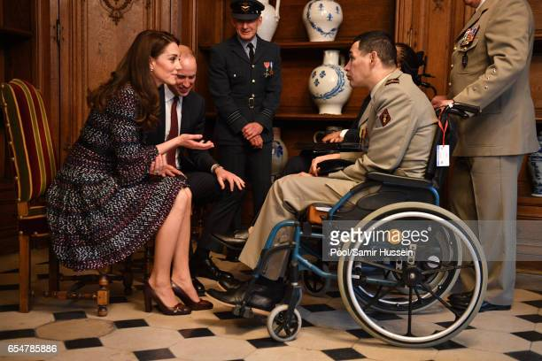 Catherine Duchess of Cambridge and Prince William Duke of Cambridge speak with wounded soldiers as they visit the Invalides on March 18 2017 in Paris...