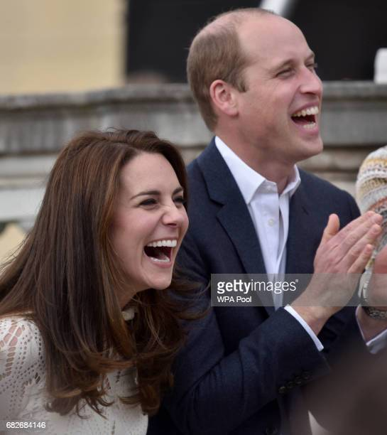 Catherine Duchess of Cambridge and Prince William Duke of Cambridge laugh as they host a tea party in the grounds of Buckingham Palace to honour the...