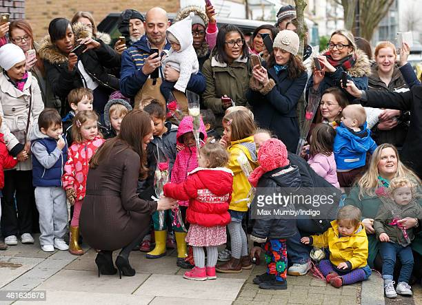 Catherine Duchess of Cambridge being photographed by member of the public using camera phones as she receives flowers from local children during an...