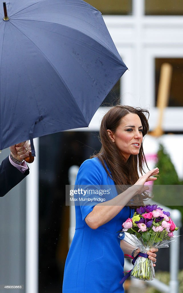 Catherine, Duchess of Cambridge being sheltered by an umbrella as she leaves Northolt High School after officially opening The ICAP Art Room on February 14, 2014 in Ealing, England.