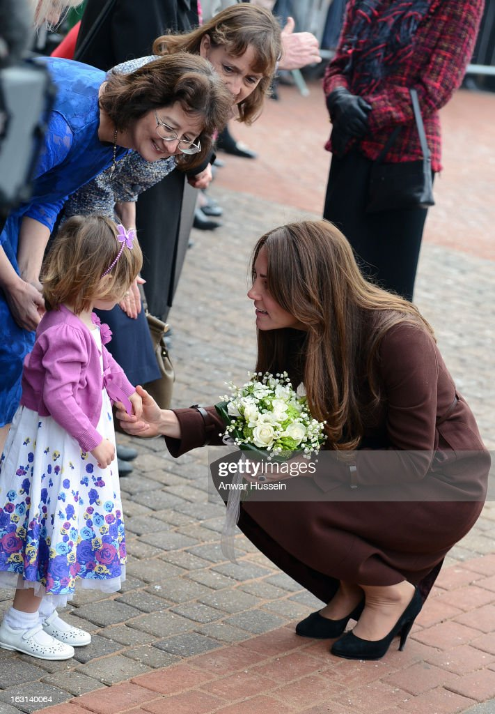Catherine, Duchess of Cambridge bends to chat to a child as she visits the National Fishing Heritage Centre during an official visit to Grimsby on March 5, 2013 in Grimsby, England.