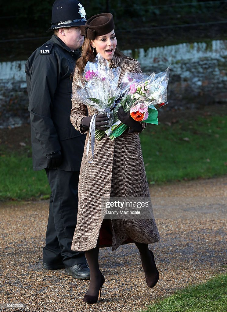 Catherine Duchess of Cambridge carries bouquets of flowers as she attends a Christmas Day church service at Sandringham on December 25 2014 in King's...