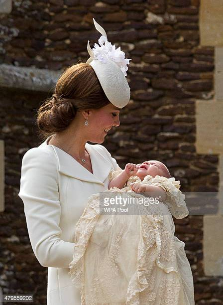Catherine Duchess of Cambridge carries Princess Charlotte of Cambridge as they arrive at the Church of St Mary Magdalene on the Sandringham Estate...