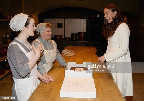 Catherine Duchess of Cambridge chats to actresses Sopie McShera and Lesley Nicol during an official visit to the set of Downton Abbey at Ealing...
