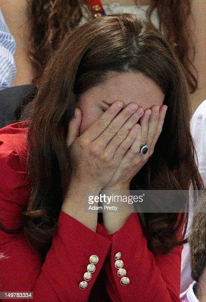 Catherine Duchess of Cambridge covers her face as she watches the swimming finals session on Day 7 of the London 2012 Olympic Games at the Aquatics...